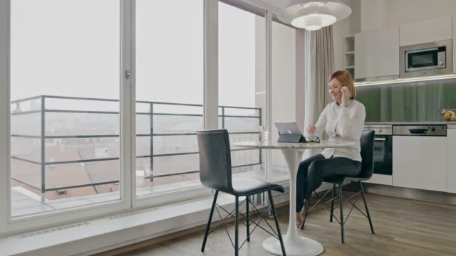 vídeos y material grabado en eventos de stock de empresaria de ws atender una llamada mientras se trabaja en una tableta digital - una mujer de mediana edad solamente