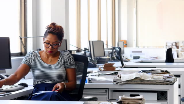 MS Businesswoman taking notes at office workstation