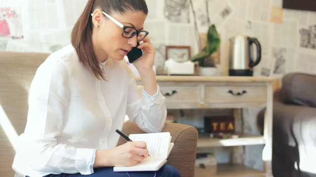 businesswoman taking notes while having a conversation on mobile phone. - personal organizer stock videos & royalty-free footage