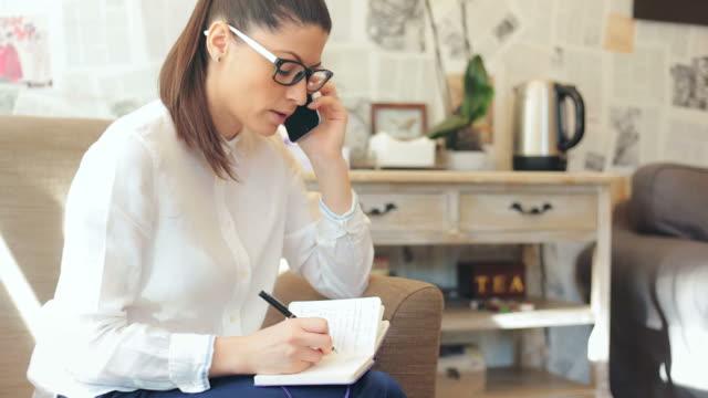 vídeos y material grabado en eventos de stock de mujer de negocios tomando notas mientras disfruta de una conversación en el teléfono móvil. - organizador personal
