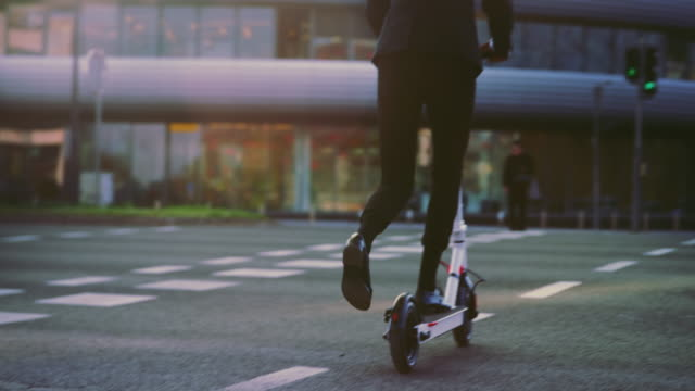slo mo businesswoman taking off on her electric scooter at the green traffic light in the city - crash helmet stock videos & royalty-free footage