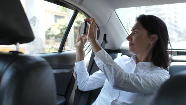 vídeos de stock, filmes e b-roll de mulher de negócios que toma a foto com o telefone esperto no táxi - passageiro