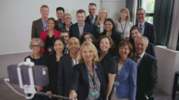 Businesswoman taking selfie with colleagues