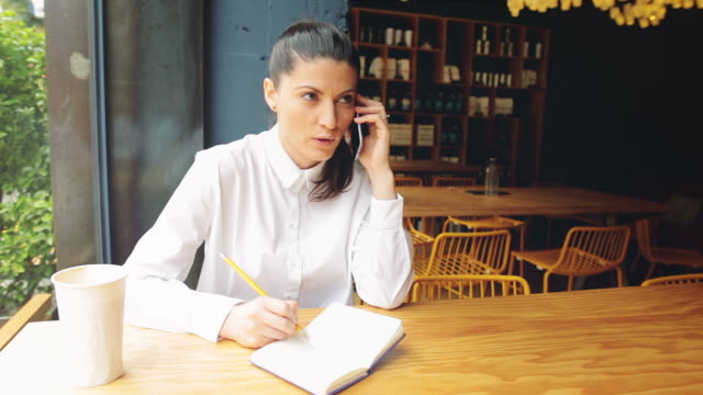 Businesswoman talking at mobile phone while taking notes.
