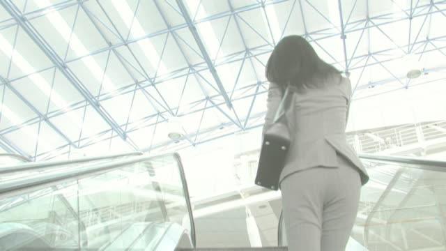 businesswoman talking on cellular phone as running up escalator - 30多歲 個影片檔及 b 捲影像