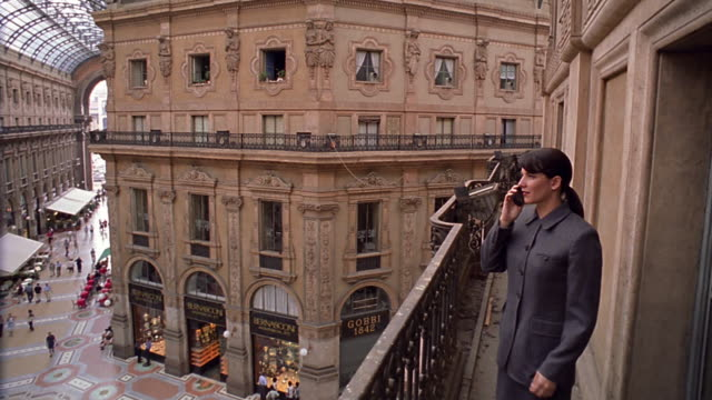 businesswoman talking on cellular phone pacing on balcony in galleria vittorio emanuele / milan - galleria vittorio emanuele ii stock videos and b-roll footage