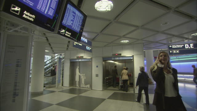 stockvideo's en b-roll-footage met ws ts ms businesswoman talking on mobile phone and looking at airport arrival and departure board / munich, germany - münchen vliegveld