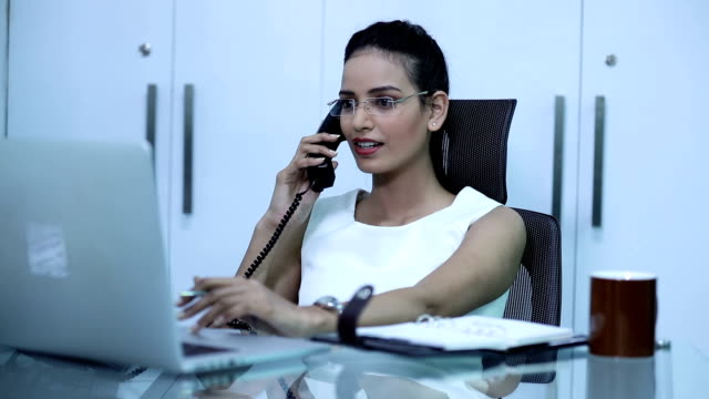 Businesswoman talking on mobile phone in the office, Delhi, India