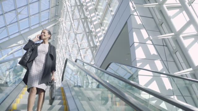 businesswoman talking on mobile phone on escalator in modern building - escalator stock videos & royalty-free footage