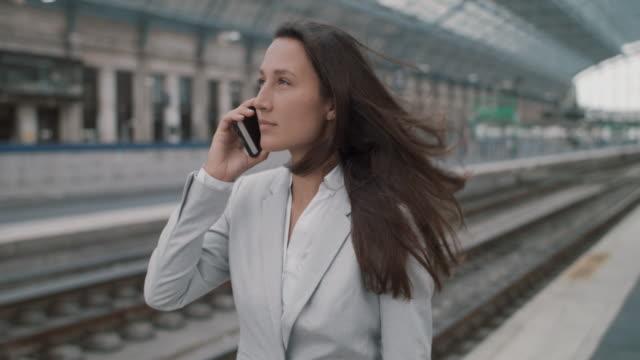 vidéos et rushes de businesswoman talking on mobile phone - quai de gare