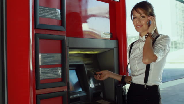 ms businesswoman talking on phone and using atm, los angeles, california, usa - suspenders stock-videos und b-roll-filmmaterial