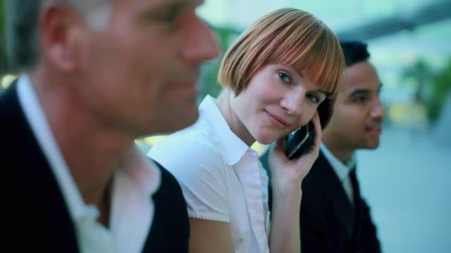cu r/f businesswoman talking on phone, sitting between two men, los angeles, california, usa - 30 34 ��r bildbanksvideor och videomaterial från bakom kulisserna