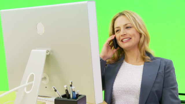 businesswoman talking on phone while using computer - only mid adult women stock videos and b-roll footage