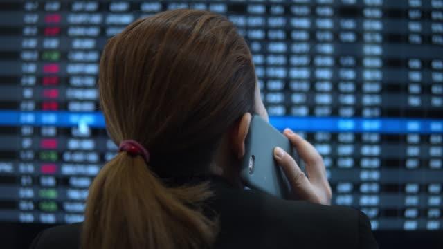 vídeos y material grabado en eventos de stock de empresaria hablando en el teléfono inteligente y mirando la pantalla financiera del mercado de valores - vendedor