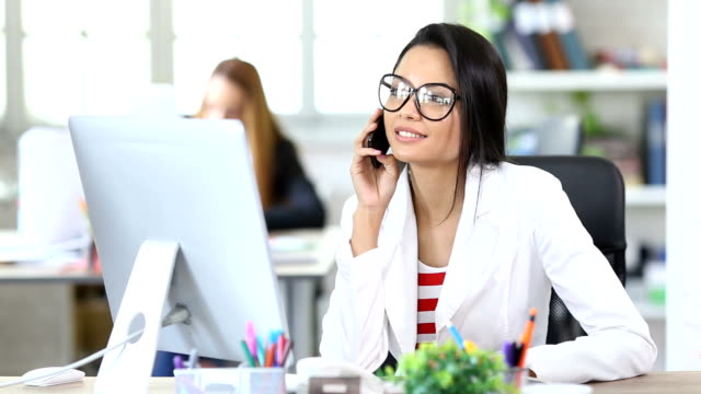 HD Businesswoman talking on smart phone in modern office