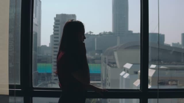 imprenditrice che parla con lo smartphone nella hall degli uffici urbani - young women video stock e b–roll