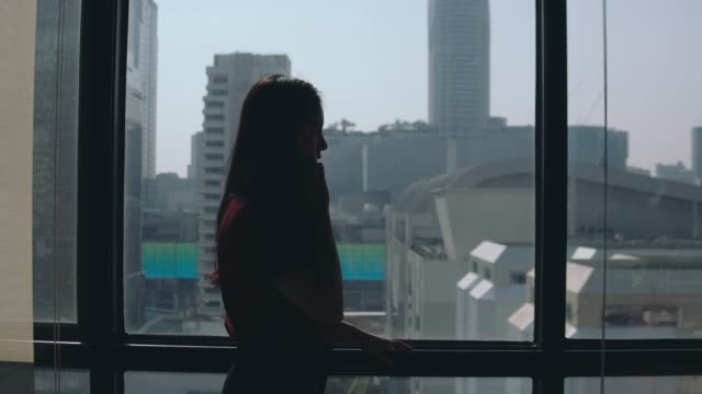 businesswoman talking on smart phone in urban office lobby - donne giovani video stock e b–roll