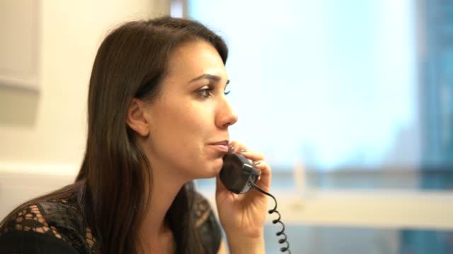 vídeos de stock, filmes e b-roll de empresária, falar ao telefone no escritório - telefone fixo