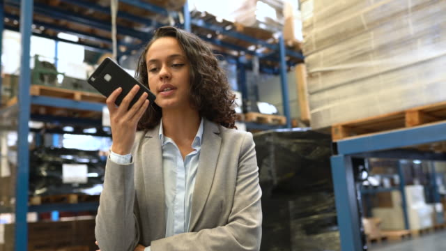 businesswoman talking over phone in warehouse - loudspeaker stock videos & royalty-free footage