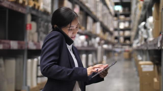 倉庫で電話を話すビジネスウーマン - 決意点の映像素材/bロール