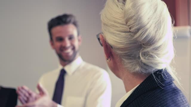 businesswoman talking to colleagues - skjorta och slips bildbanksvideor och videomaterial från bakom kulisserna