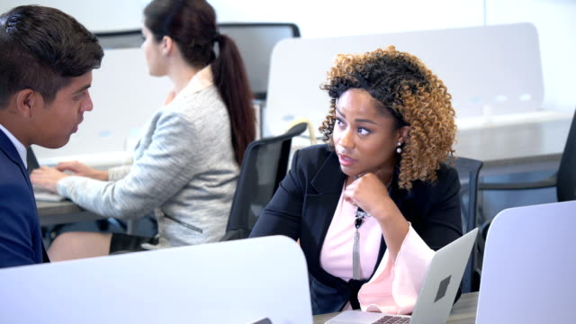 businesswoman talking to coworker in busy office - pacific islander background stock videos & royalty-free footage