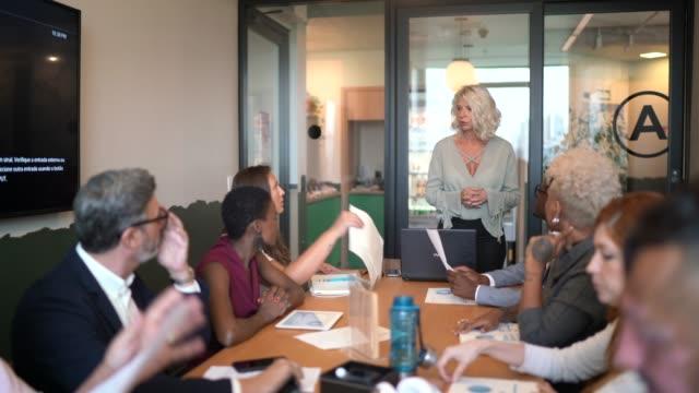 vídeos de stock e filmes b-roll de businesswoman talking to his colleagues on presentation in the office - discurso