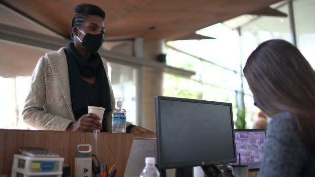 geschäftsfrau im gespräch mit rezeptionistin am eingang der bürolobby - mit gesichtsmaske - sekretärberuf stock-videos und b-roll-filmmaterial