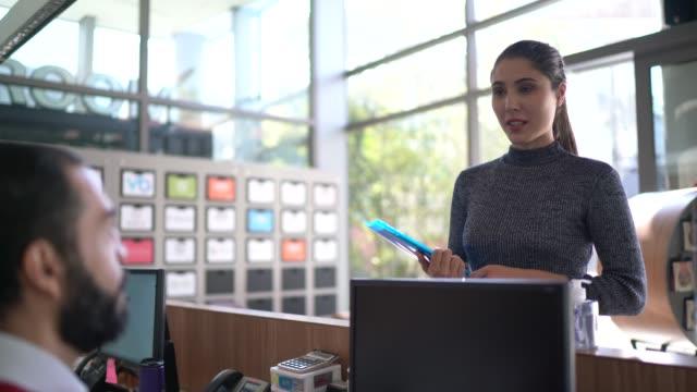 vídeos y material grabado en eventos de stock de empresaria hablando con recepcionista en la entrada del vestíbulo de la oficina - entrevista acontecimiento