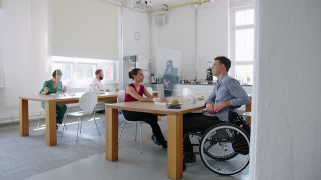 businesswoman talking with coworker person with disabilities - canteen stock videos & royalty-free footage