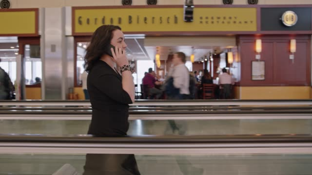businesswoman talks on phone while traveling down moving walkway in airport terminal. - wheeled luggage stock videos & royalty-free footage