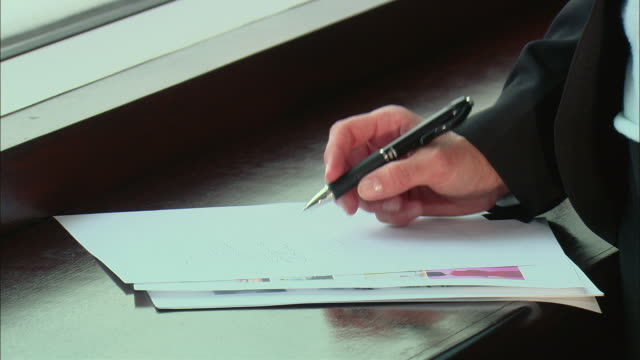 CU ZI Businesswoman tapping her pen and writing notes on paper / Rye Brook, New York, USA