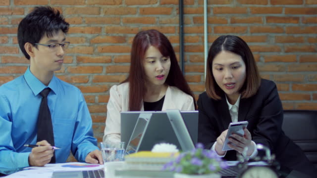 businesswoman team leader checking and analyze graph of her teammate with smartphone , dolly shot right to left - five people stock videos and b-roll footage
