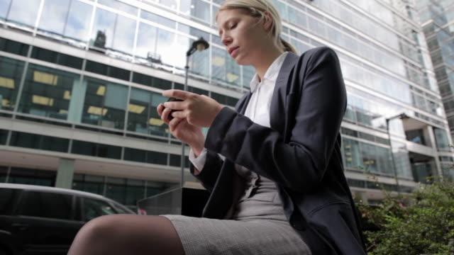 businesswoman text messaging on cellphone in city - nordeuropäischer abstammung stock-videos und b-roll-filmmaterial