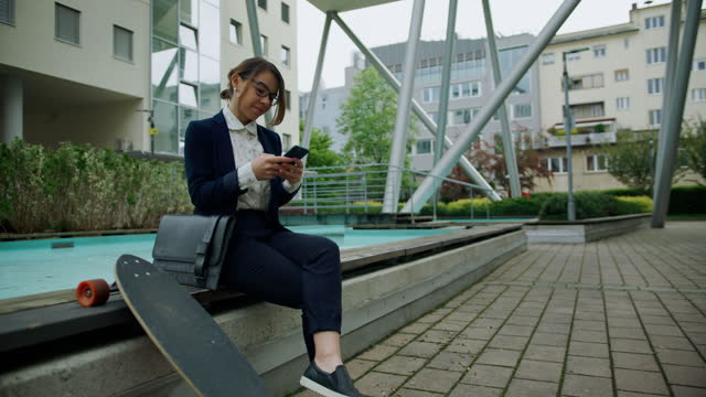 businesswoman text messaging on smart phone while sitting beside fountain - 1 minute or greater stock videos & royalty-free footage
