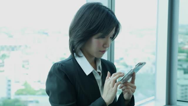 vidéos et rushes de femme d'affaires sms gsm au bureau - une seule femme d'âge moyen