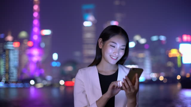 MS businesswoman texting on her phone at night in Shanghai