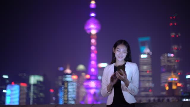 WS businesswoman texting on her phone at night, Shanghai, China