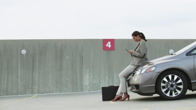 vídeos de stock e filmes b-roll de businesswoman texting on mobile phone in car park - parking