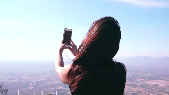 businesswoman travel use smartphone taking photo on mountain top