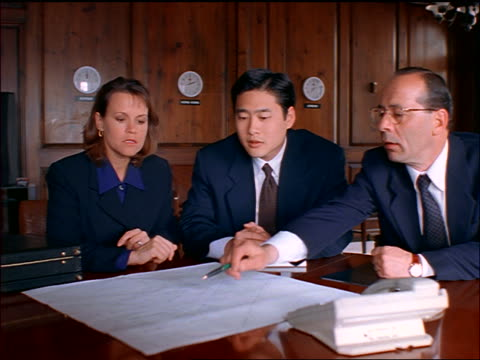 businesswoman + two businessmen (one asian) discuss chart/blueprints on table in conference room - femmina con gruppo di maschi video stock e b–roll