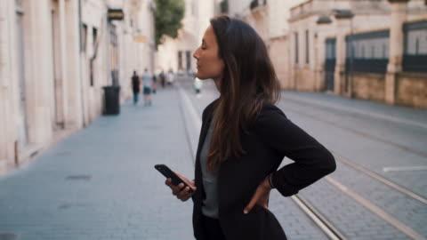 vidéos et rushes de businesswoman typing on cell phone standing in historic part of town - tenue soignée