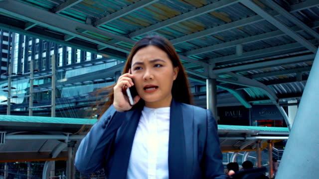 vídeos de stock, filmes e b-roll de empresária usar um telefone em uma cidade, câmera lenta - etnia caucasiana