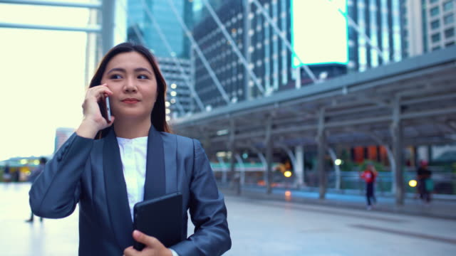 Businesswoman use a phone in a city,Tracking shot