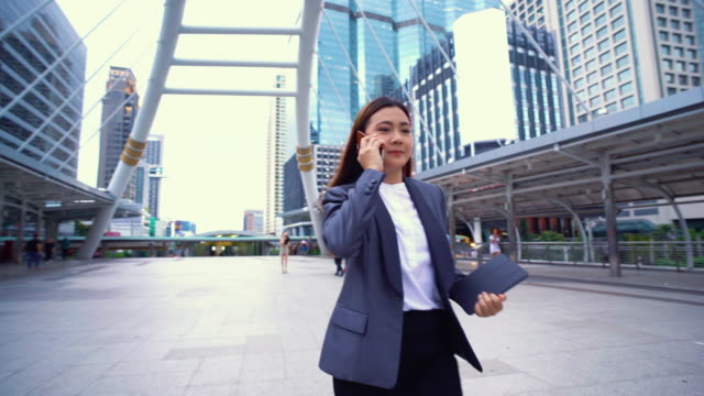 businesswoman use a phone in a city,tracking shot - businesswoman stock videos & royalty-free footage