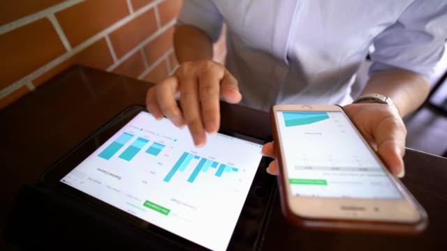 vídeos de stock, filmes e b-roll de empresária usar tablet e smartphone para o negócio - gráfico