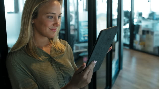 businesswoman using a digital tablet at a modern office business space. - using digital tablet stock videos & royalty-free footage