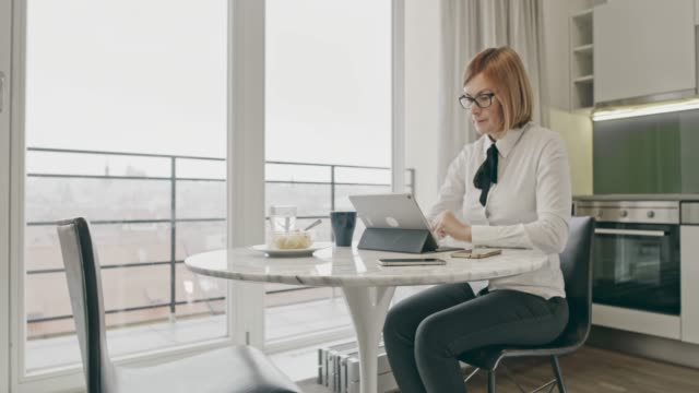 WS Businesswoman using a digital tablet at home