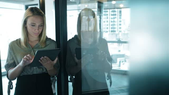 オフィスでデジタルタブレットを使用しているビジネスウーマン。 - casual clothing点の映像素材/bロール