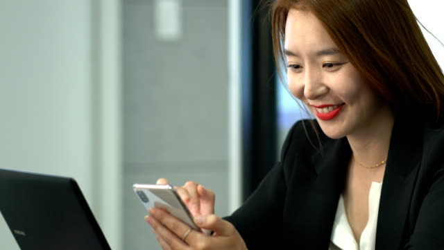 A businesswoman using a smart phone in the meeting room